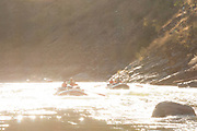 Sunrise glares off the  water during morning in The Impassible Canyon on the Middle Fork of the Salmon River during six day rafting vacation, Idaho.