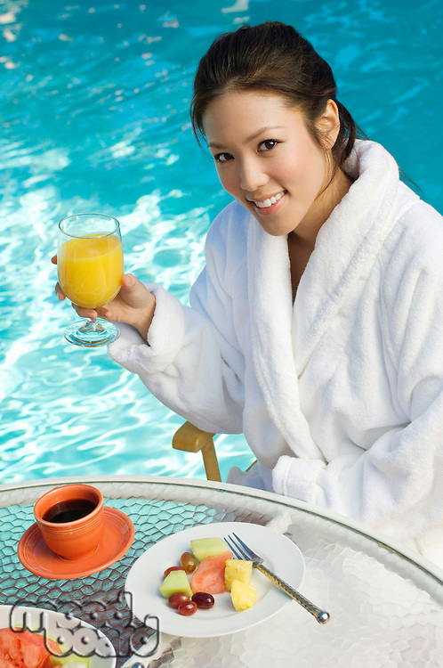 Young Chinese woman drinking orange juice by swimming pool, portrait