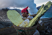 BONDOWOSO, EAST JAVA - DECEMBER 17: A miner bears a pair of sulfur full-basket during annual sacrificial ritual held in Ijen sulfur crater, Bondowoso, East Java, Indonesia, December 17, 2013. The miners held the sacrifice in order to ask blessing of good result and prevent from accident or injury. The tradition begun in 1978 after a tragedy that killed four people and fourteen black out cause of poisoning gas. Daily miners produce fifteen ton of sulfur or approximately 450 ton a month. Come close to 150 miners work everyday. All the sulfur goes to sugar factory ans used as sugar whitening.