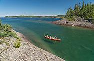 Family canoeing near Devils Warehouse Island at Lake Superior Provincial Park, Ontario, Canada.