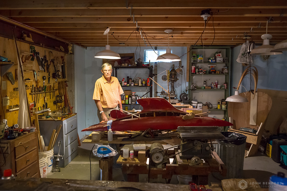 A woodworking hobbyist poses with a toy boat he is making in his basement workshop.