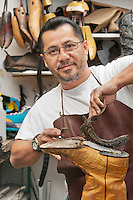 Portrait of a happy shoemaker removing sole in workshop