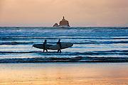 Surfers and Tillamook Rock Light House, Oregon.