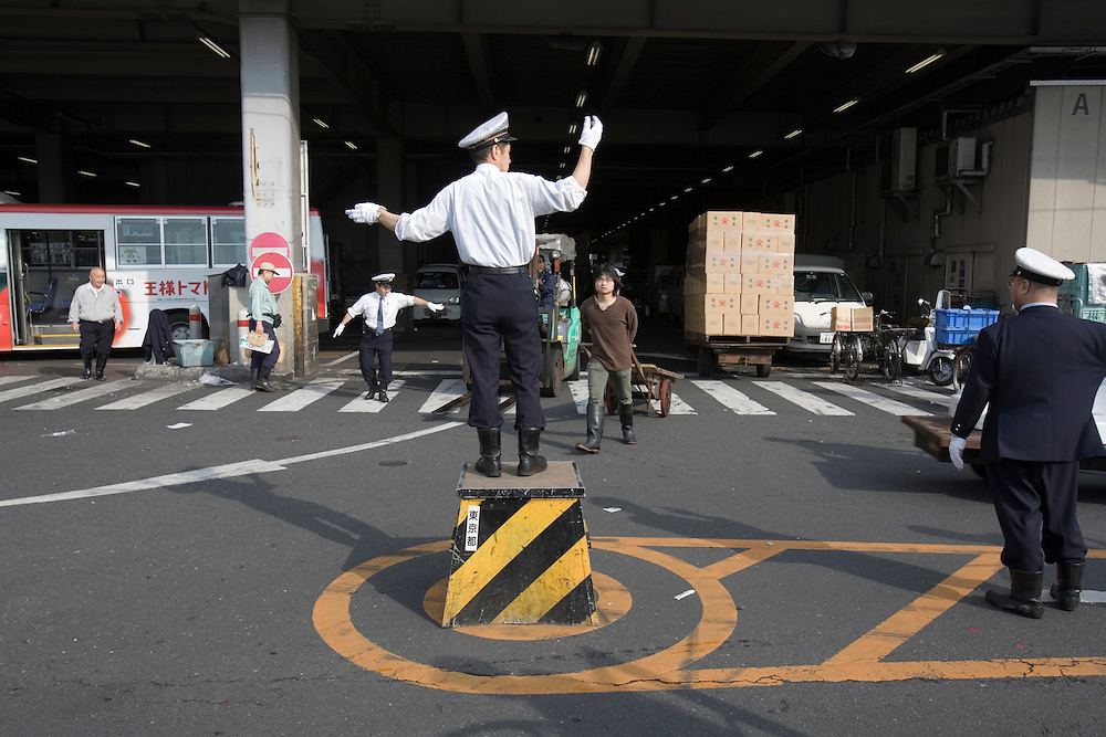 Asia, Tokyo, Japan, Policeman directs traffic at Tsikuju Fish Market before dawn
