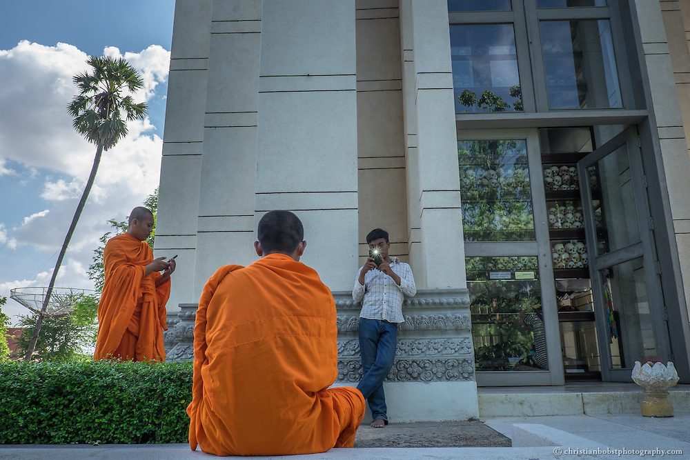 Junge Mönche machen vor der Stupa in Gedenkstätte Choeung Ek in Phnom Penh Selbstportraits. Im Todeslager S-21, welche etwas ausserhalb der Stadt liegt, wurden während des brutalen Regimes der Roten Khmer zwischen 1975 bis 1979 über zwölftausend Menschen gefoltert und ermordet. In nur 4 Jahren brachten die Roten Khmer ein bis zwei Millionen Kamodschaner  auf brutalste Art ums Leben.