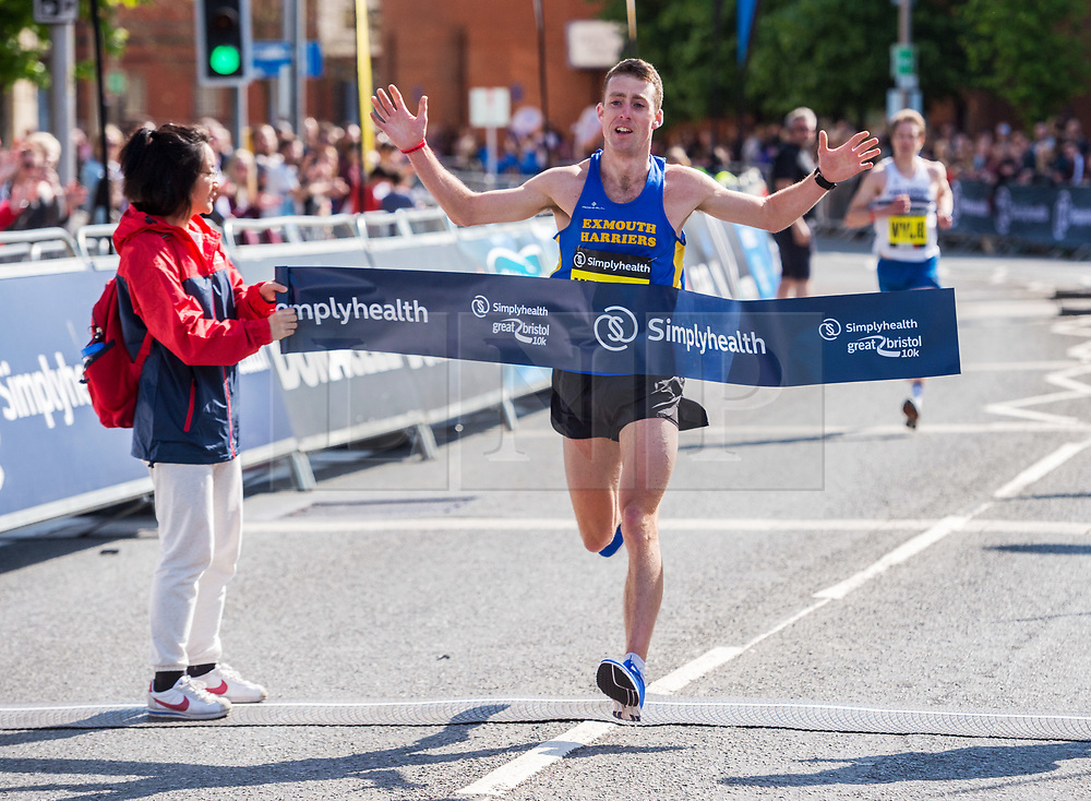 © Licensed to London News Pictures. 13/05/2018. Bristol, UK. TOM MERSON is first to cross the finish line in the Simplyhealth Great Bristol 10k run, ending in 2nd place. 13,000 runners are set to take part. Starting on Anchor Road near Bristol Cathedral, they'll be set off by 2018 Olympic Winter Medallist Dom Parsons, who took home bronze in the skeleton race this January. 30 firefighters are running the Great Bristol 10k this weekend in full fire apparatus while carrying one of their ladders to raise money for three-year-old Daisy Bowyer, who has cerebral palsy and relies on the use of a walking frame and wheelchair. They hope to raise over £20,000 to pay for a private operation that would allow her to walk unaided. The group will run the 10k course with the six-metre long ladder and fire kit, weighing 30kg per firefighter. Photo credit: Simon Chapman/LNP