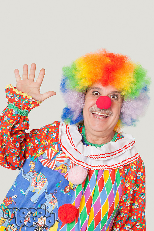 Portrait of cheerful senior male clown waving hand over gray background