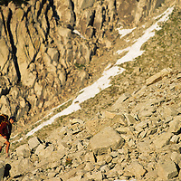 Mountaineer hiking through talus at the base of the massive Lone Peak Cirque, Utah