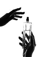 detail close-up silhouette in shadow of a  woman hands holding perfume in studio on white background isolated