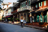 A man rides a bicicyle on the streets of Luang Prabang, Laos.