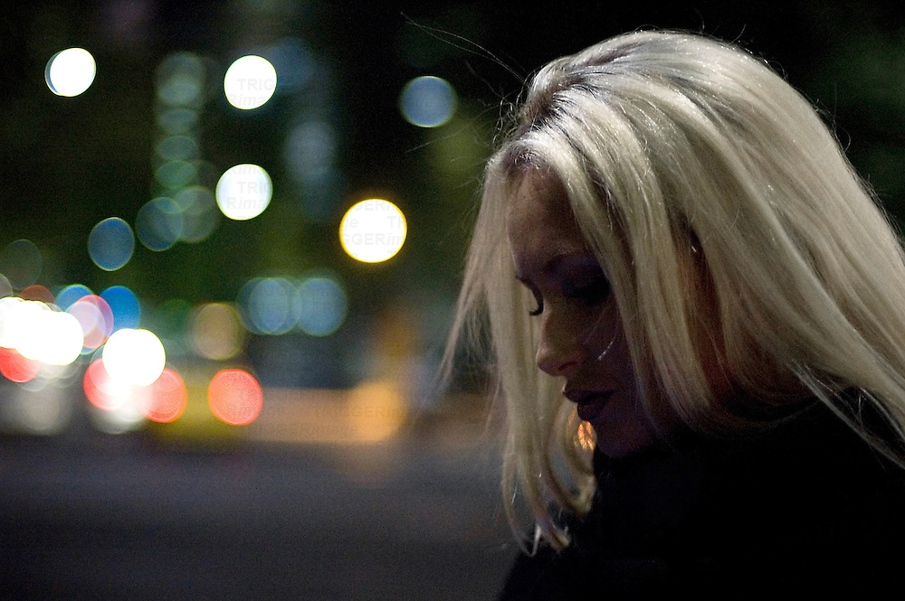 Young woman in profile with blonde hair standing on the street at night