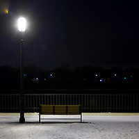 A park bench illuminated by a light and surrounded by a dusting of snow at the Keyport Waterfront park in Keyport New Jersey.