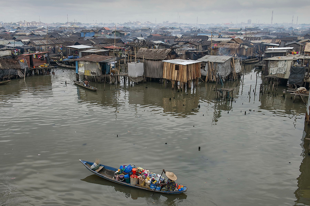 A vendor, with a miriad of goods packed onto their boat, paddles about looking for customers in Makoko