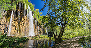Mali Prstavac waterfall plunges 18 meters at the Upper Lakes (Gornja Jezera). Plitvice Lakes National Park (Nacionalni park Plitvicka jezera, in Croatia, Europe) was founded in 1949 and is honored by UNESCO as World Heritage Site. Waters flowing over limestone, dolomite, and chalk in this karstic landscape have, over thousands of years, deposited travertine barriers, creating natural dams, beautiful lakes and waterfalls. Warming conditions after the last Ice Age (less than 12,000 years ago) allowed the natural dams to form from tufa (calcium carbonate) and chalk depositing in layers, bound by plants. Plitvicka Jezera is a municipality of Lika-Senj County, in the Republic of Croatia. This panorama was stitched from 7 overlapping photos.