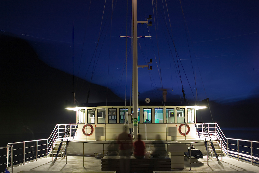 New Zealand, South Island, Fiordland National Park, Passengers on deck of M/V Fiordland Navigator anchored under steep mountain walls along Doubtful Sound at dusk on summer evening