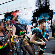 Hackney carnival 2014. The procession started in Ridley Road and passed by the The Hackney Town Hall with thousands of spectators lining the road. Dancers wearing blue,white and black feathered head gear grind their way passed the Local Sainsbury's.