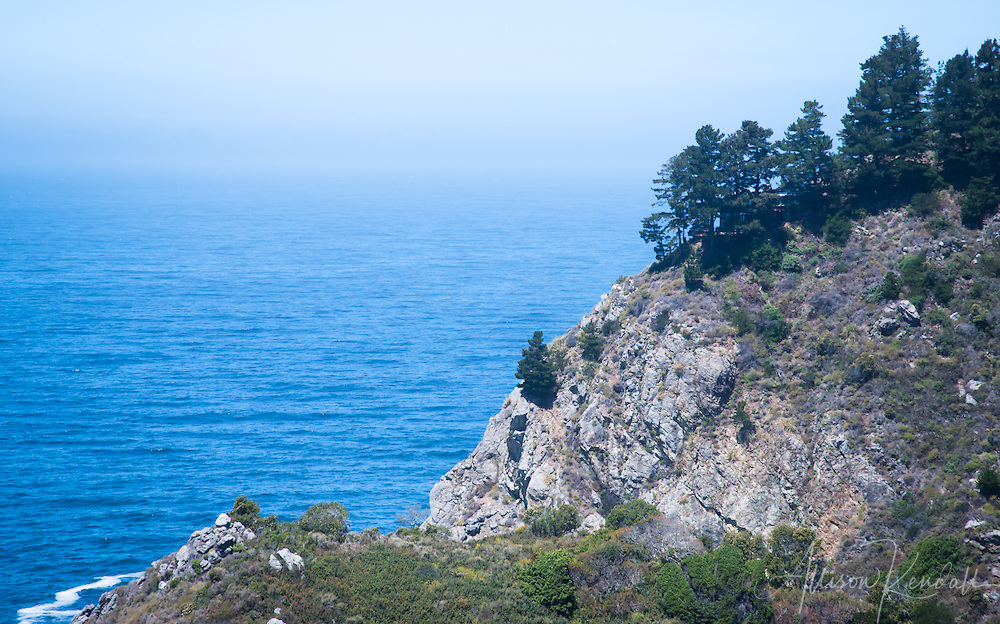 Blue ocean water contrasts with the rocky mountain cliffs of Big Sur on a misty summer day
