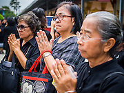 19 OCTOBER 2014 - BANG BUA THONG, NONTHABURI, THAILAND: Women pray at Apiwan Wiriyachai's cremation at Wat Bang Phai in Bang Bua Thong, a Bangkok suburb, Sunday. Apiwan was a prominent Red Shirt leader. He was member of the Pheu Thai Party of former Prime Minister Yingluck Shinawatra, and a member of the Thai parliament and served as Yingluck's Deputy Prime Minister. The military government that deposed the elected government in May, 2014, charged Apiwan with Lese Majeste for allegedly insulting the Thai Monarchy. Rather than face the charges, Apiwan fled Thailand to the Philippines. He died of a lung infection in the Philippines on Oct. 6. The military government gave his family permission to bring him back to Thailand for the funeral. His cremation was the largest Red Shirt gathering since the coup.     PHOTO BY JACK KURTZ