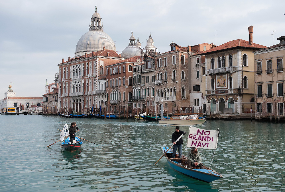 """VENICE, ITALY - JANUARY 16:  Protesters sailing on the Grand Canal hold  banners reading """"Stop the large Ships""""  on the day of the special meeting discussing the environmental impact of cruises in Venice on January 16, 2012 in Venice, Italy. Protest are mounting in Venice against large cruise ships crossing St Marks's basin after the Costa Concordia tragedy."""