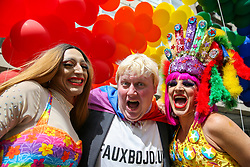 © Licensed to London News Pictures. 06/07/2019. London, UK. Two participants with a man dressed as Conservative Party leadership contender Boris Johnson MP poses for photographs under the rainbow coloured balloons during the annual Pride Parade in central London. Photo credit: Dinendra Haria/LNP