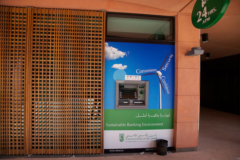 Masdar City. ASIEN, VEREINIGTE ARABISCHE EMIRATE, EMIRAT ABU DHABI, ABU DHABI, 22.05.2011: Geldautomat der National Bank of Abu Dhabi. Neben der Bankfiliale gibt es unter anderem ein Sushi-Restaurant und einem Oekoladen auf dem Campus. Die Wu?stenstadt Masdar sollte das Silicon Valley fu?r nachhaltige Technologien werden. 2006 rief Scheich Mohammad Bin Zayed al-Nahyan, Kronprinz von Abu Dhabi, das Projekt ins Leben. Die Fertigstellung des Projekts wird sich verzoegern: statt wie geplant 2016 wird die Oekostadt fruehestens 2025 fertig. - Stichworte: Nachhaltigkeit, Masdar, City, Emirat, Vision, Zukunft, Arabien, Stadt, Oekologie, Gruen, Planung, Foster, Architekt, Wueste, Umwelt, Technik, Universitaet, Bank, Automat, Geldautomat, Campus
