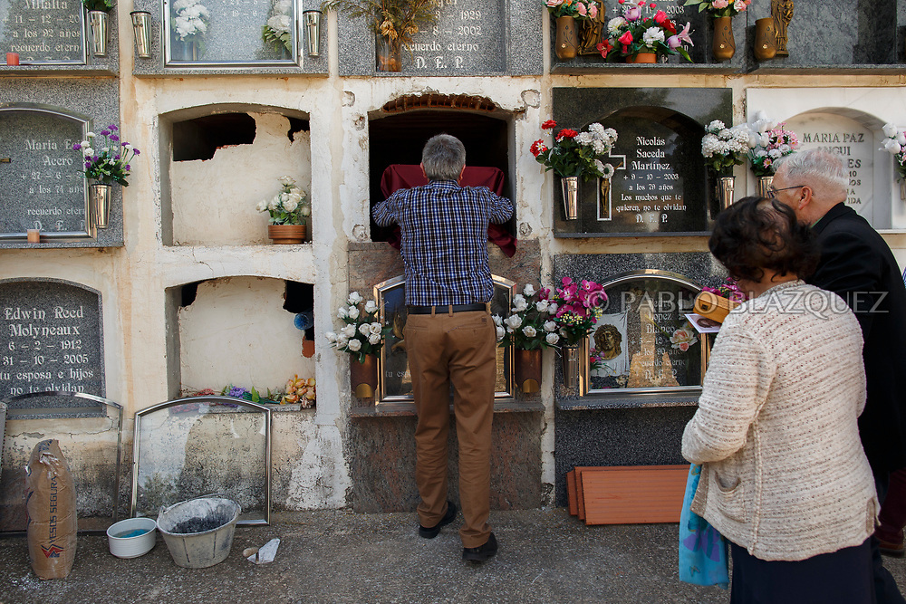 19/05/2018. A relative places the remains of Valentin Alcantarilla Mercado who was assassinated by dictator Francisco Franco's forces inside a niche during his burial at the cemetery on May 19, 2018 in Sacedon, Guadalajara province, Spain. General Franco's forces killed Timoteo Mendieta and other people between 1939 and 1940 after Spain's Civil War and buried them in mass graves in Guadalajara's cemetery. Argentinian judge Maria Servini used the international human rights law and ordered the exhumation and investigation of Mendieta's mass grave. The exhumation was carried out by Association for the Recovery of Historical Memory (ARMH) recovering 50 bodies from 2 mass graves and identified 24 of them. Spain's Civil War took the lives of thousands of people on both sides, but Franco continued his executions after the war has finished. Spanish governments has never done anything to help the victims of the Civil War and Franco's dictatorship while there are still thousands of people missing in mass graves around the country. (© Pablo Blazquez)