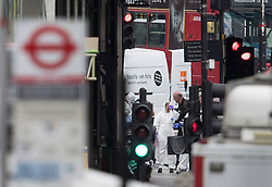 © Licensed to London News Pictures. 04/06/2017. London, UK. Forensics officers are seen near a van believed to have been driven by the attackers next to an abandoned London bus near Borough Market - after an attack by three men killed seven and injured at least 48. Police shot three attackers dead after they deliberately drove their van at people on London Bridge and then stabbed drinkers at bars in nearby Borough Market. Photo credit: Peter Macdiarmid/LNP