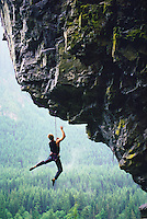 Man hanging from an overhanging rock.