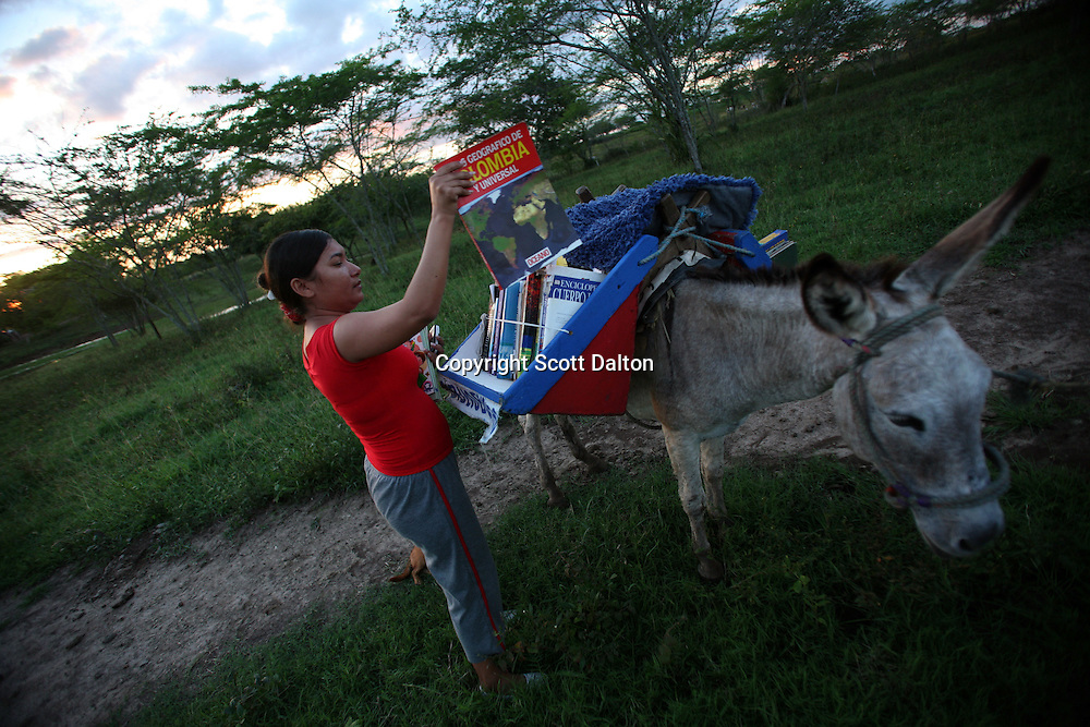 Madelis España Ariza, age 30, pulls a book out from the shelf of the Biblioburro, or Donkey Library, in El Brasil, in northern Colombia on Saturday, October 11, 2008. (Photo/Scott Dalton)