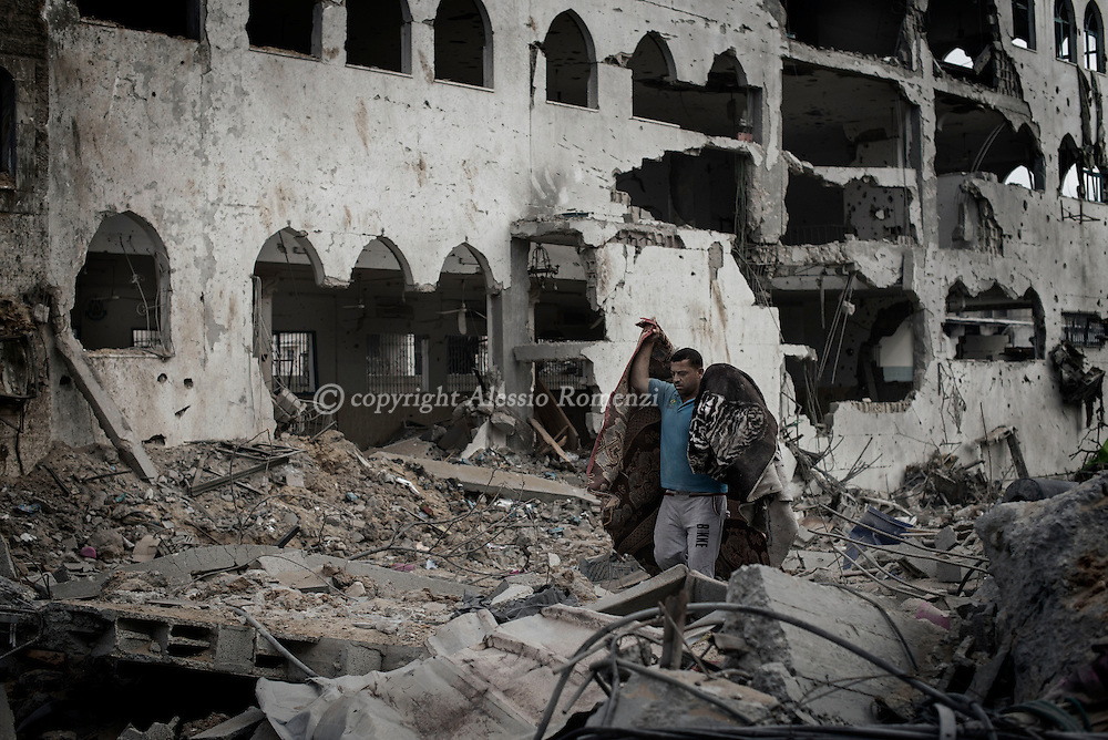 Gaza Strip, Gaza City: A Palestinians man carries blankets among rubble in Shujayeh neighbourhood during a 72 hours ceasefire on August 11, 2012. ALESSIO ROMENZI