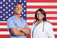 Portrait of confident mixed race male and female surgeons over American flag
