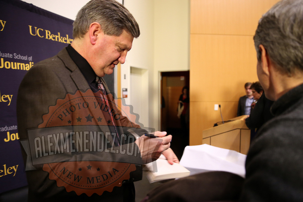 """Reporter James Risen signs a copy of his book after speaking at the """"Prosecuting the Press"""" event at the UC Berkeley Graduate School of Journalism in Berkeley, California, on Thursday, November 14, 2013. Risen, the New York Times national security reporter is facing jail for refusing to comply with a subpoena to reveal his sources in relation to his book titled State of War: The Secret History of the CIA and the Bush Administration. (AP Photo/Alex Menendez)"""