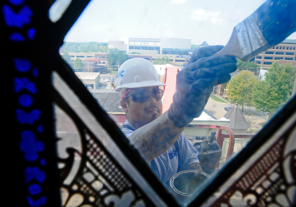 Jaime Sepeda of Builders Sales & Service paints the frame of a stained-glass window in the steeple of the First Lutheran Church in downtown Moline on Friday, August 19.  For over three weeks, Sepeda and his team have been touching up the exterior of the church, which was built in 1875.