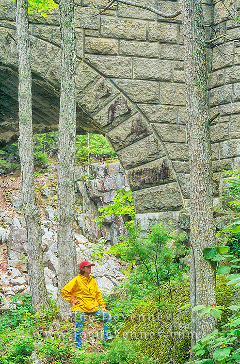 Hiker by a carriage road bridge. Acadia National Park. Maine