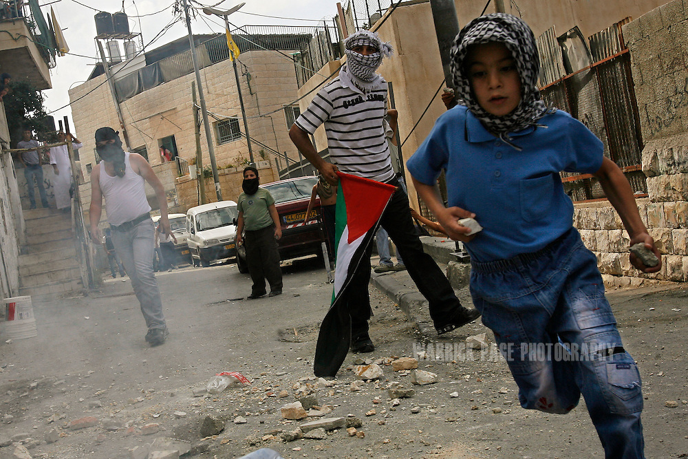 JERUSALEM - OCTOBER 9: A Palestinian boy runs with rocks in his hands during violent clashes on Friday, October 9, 2009, in the East Jerusalem neighbourhood of Ras al-Amud. Violent clashes continued in East Jerusalem and parts of the West Bank amidst calls from the militant Islamic group Hamas for a Day of Rage to defend the al-Aqsa mosque, Islam's third holiest site.  (Photo by Warrick Page)
