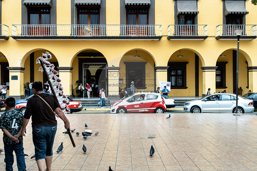 People walk past the city municipal building called the Palacio Municipal San Andres Tuxtla in San Andres Tuxtlas, Veracruz, Mexico.