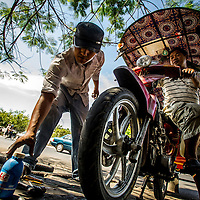 Jan 3, 2013 - A repair shop employee makes repairs to a aling tuktuk in the Cambodian capital city of Phnom Penh.<br /> <br /> Story Summary: Amidst the feverish pace of Phnom Penh&rsquo; city streets, a workhorse of transportation for people and goods emerges: Bicycles, motorcycles, scooters, Mopeds, motodups and Tuk Tuks roam in place of cars and trucks. Almost 90 percent of the vehicles roaming the Cambodian capital of almost 2.3 million people choose these for getting about. Congestion and environment both benefit from the small size and small engines. Business is booming in the movement of goods and and another one million annual tourists in Cambodia&rsquo;s moto culture.