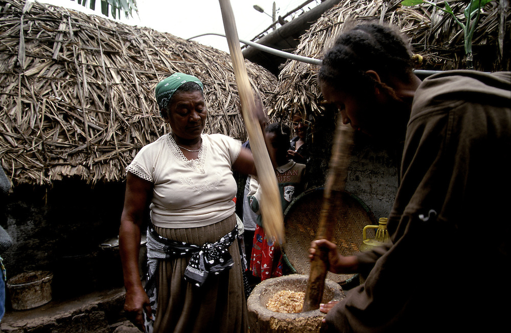 Women smashing corn to make flour.  The northeast area of Santo Antao has a microclimate that makes it the only part of the archipelago where it rains regularly and where many vegetables and fruits grow.