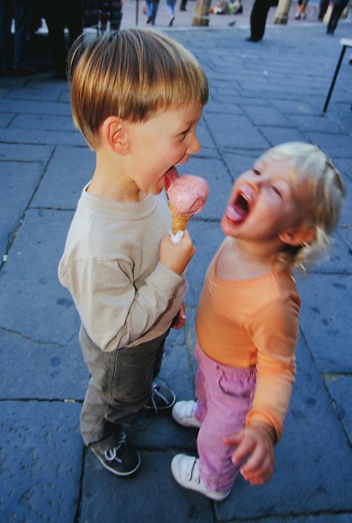Europe, Italy, Sienna, children eating ice cream (gelatto) in plaza.  MR