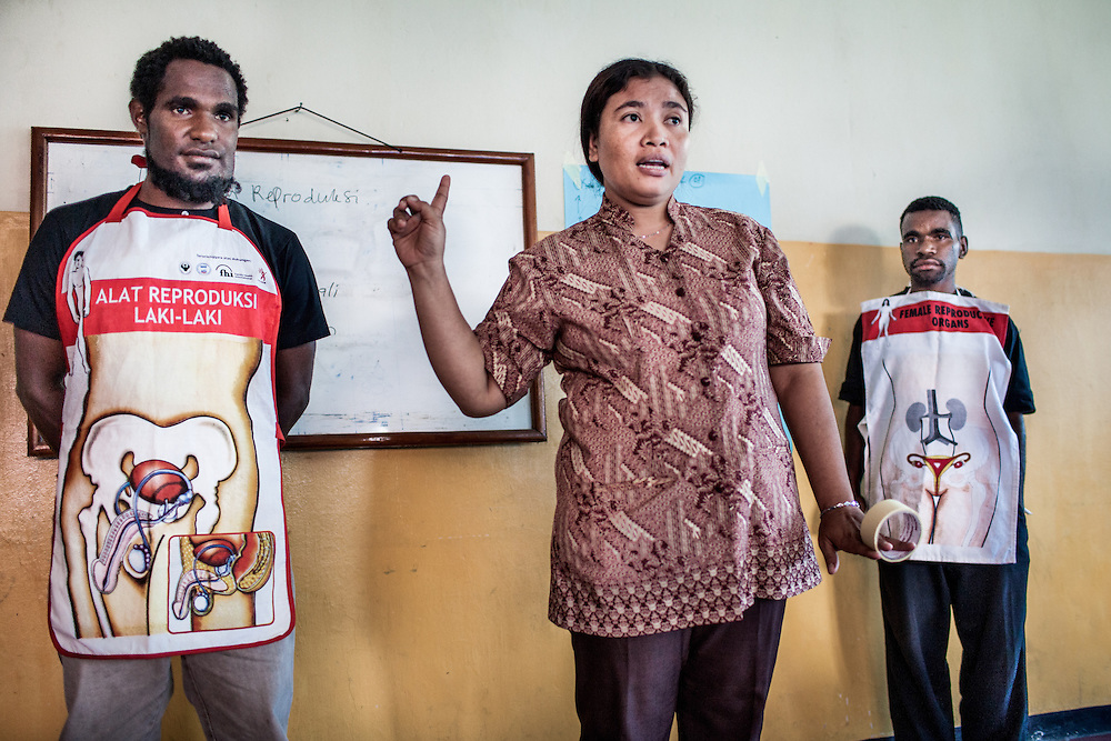 L-R: Roni (26) and Mecky (18), each wearing an apron with a diagram of the male and female reproduction organs, participate in a sexual reproduction and HIV/AIDS educational training conducted by the Public Health Development Foundation (YPKM).<br /> <br /> In Papua young teenagers are already having sex but HIV/AIDS education are still lacking. GIDI Baptist Church invited teenagers from surrounding villages in Wamena for a weeklong crash course on sex education, family planning, condom, sexual transmitted diseases (STD), and HIV/AIDS. These young adults will return to their villages to serve as peer counselors and provide information and support. However, despite the program's effectiveness, YPKM is lacking funding to continue this important educational course.<br /> <br /> For many Papuan youths, their first sexual encounter can take place during their early teenage years.  Some are sexually active by the time they reach puberty.  Life Skills Education (LSE), a curriculum designed by UNICEF that provides education on human reproduction, pregnancy, sex, Sexual Transmitted Diseases, and HIV/AIDS is taught in many high schools throughout Papua.  However, this essential educational course is mainly available in schools located in cities but not in rural areas.  Moreover, LSE does not reach many indigenous Papuan youths because many of them are not able to attend high school.  In most cases teachers responsible for teaching this course lack sufficient training and essential materials, such as books with up-to-date information and visual aids, to adequately educate their students.  They often encourage their students to seek additional information on the Internet.  Also, detailed information on condoms is regularly excluded in lectures and reading materials because of the general perception that it will endorse pre-marital sex.  As a result, students carry incomplete information, misconceptions and misunderstandings into adulthood, which increases their vulnerability to