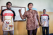 L-R: Roni (26) and Mecky (18), each wearing an apron with a diagram of the male and female reproduction organs, participate in a sexual reproduction and HIV/AIDS educational training conducted by the Public Health Development Foundation (YPKM).<br />
