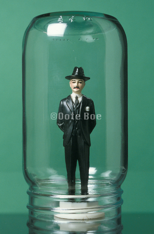 business doll under a glass jar
