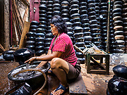 "28 MARCH 2017 - BANGKOK, THAILAND: A woman washes newly made monks' bowls, called ""bat"" (pronounced with a long ""a"" as in baat) on Soi Baan Bat in Bangkok. The bowls are made from eight separate pieces of metal said to represent the Buddha's Eightfold Path. The Monk's Bowl Village on Soi Ban Baat in Bangkok is the only surviving one of what were originally three artisan's communities established by Thai King Rama I for the purpose of handcrafting ""baat"" the ceremonial bowls used by monks as they collect their morning alms. Most monks now use cheaper factory made bowls and the old tradition is dying out. Only six or seven families on Soi Ban Baat still make the bowls by hand. Most of the bowls are now sold to tourists who find their way to hidden alleys in old Bangkok. The small family workshops are only a part of the ""Monk's Bowl Village."" It is also a thriving residential community of narrow alleyways and sidewalks. The area is also spelled Ban Bat or Baan Bat.           PHOTO BY JACK KURTZ"