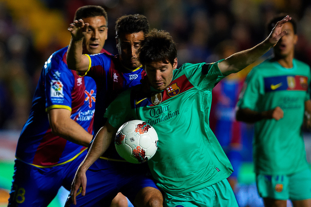 Levante's Pedro Lopez (C) vies for the ball with FC Barcelona's Lionel Messi (R) during the Spanish league football match Levante UD vs FC Barcelona on April 14, 2012 at the Ciudad de Valencia Stadium in Valencia. (Photo by Xaume Olleros/Action Plus)