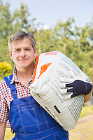 Portrait of confident gardener carrying sack in plant nursery
