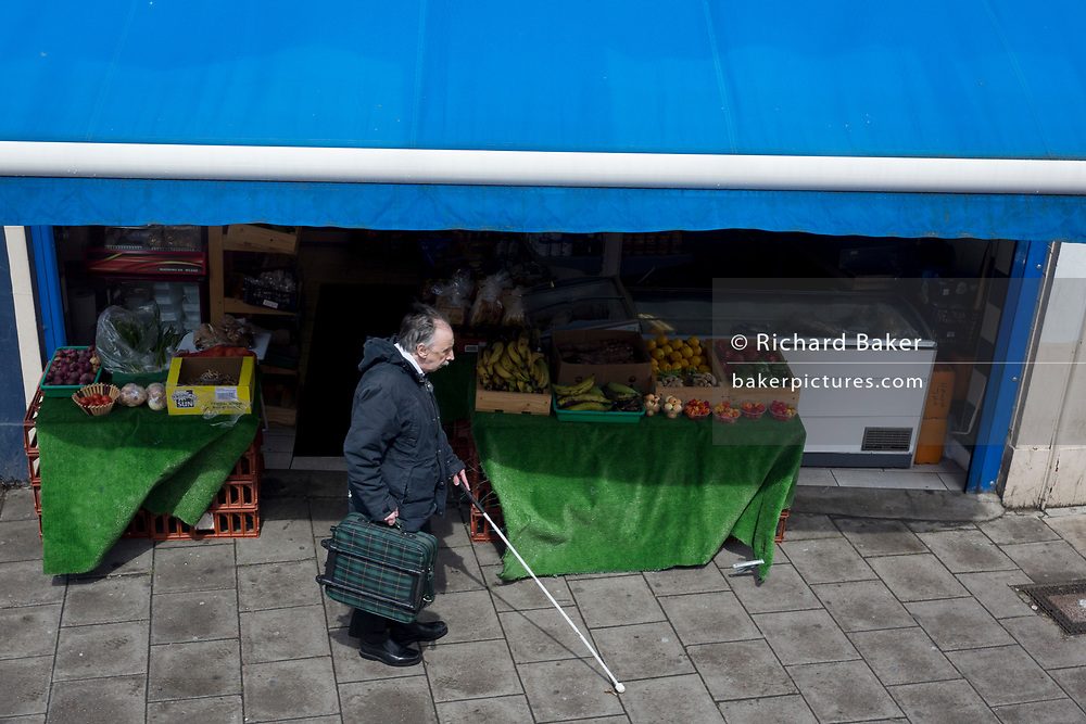 An unsighted man walks with the aide of a white stick passing a local fruit and veg shop, on 8th May 2019, in London, England.