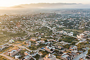 Morning fog rises over San Miguel de Allende, Mexico at dawn with the Bajio Mountains behind.
