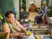 20 APRIL 2013 - BANGKOK, THAILAND:   A woman cuts mango in front of her home in Talat Noi (Talat means Market, Noi means Small. Literally Small Market). The Talat Noi neighborhood in Bangkok started as a blacksmith's quarter. As cars and buses replaced horse and buggy, the blacksmiths became mechanics and now the area is lined with car mechanics' shops. It is one the last neighborhoods in Bangkok that still has some original shophouses and pre World War II architecture. It is also home to a  Teo Chew Chinese emigrant community.   PHOTO BY JACK KURTZ