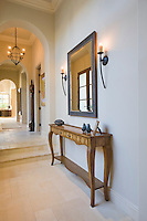 Antique console table with grey framed mirror in hallway