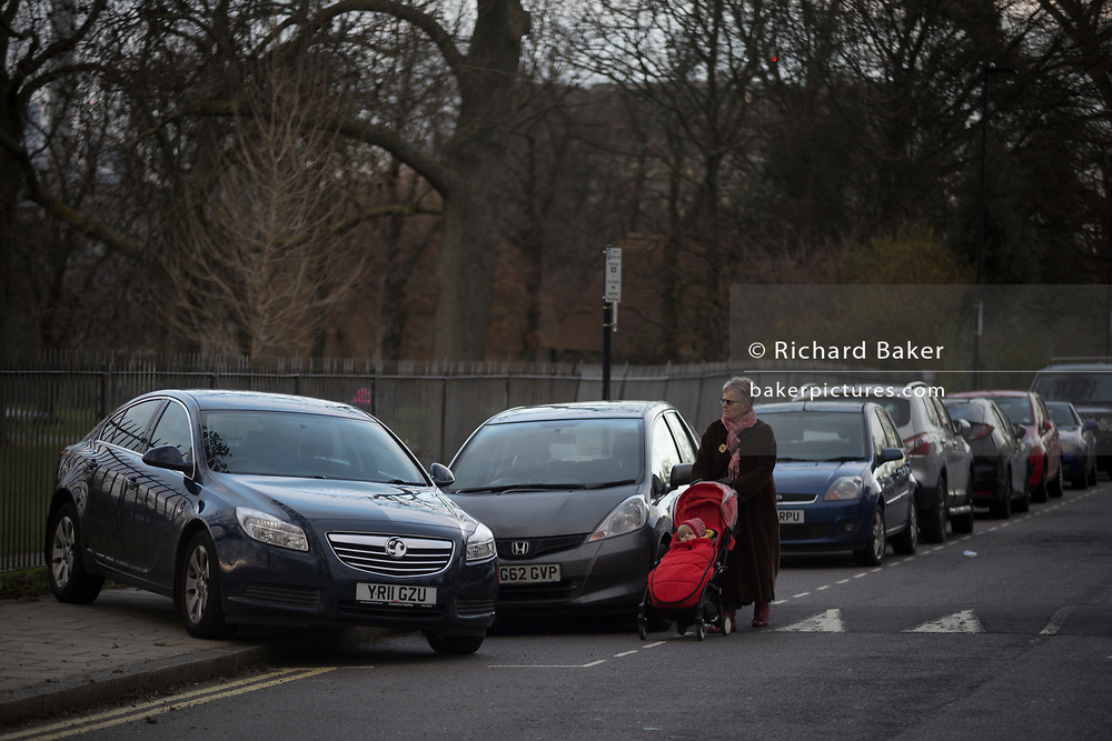An elderly lady with a child's buggy walks in the road past a mysteriously abandoned Vauxhall car resting at 45 degrees, off the road but blocking a pavement on Ruskin Park, on 2nd February 2018, in Southwark, London, England.